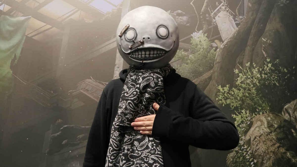 Fotografia che ritrae il famoso ed eccentrico game director Yoko Taro, con in testa l'iconica maschera di Emil