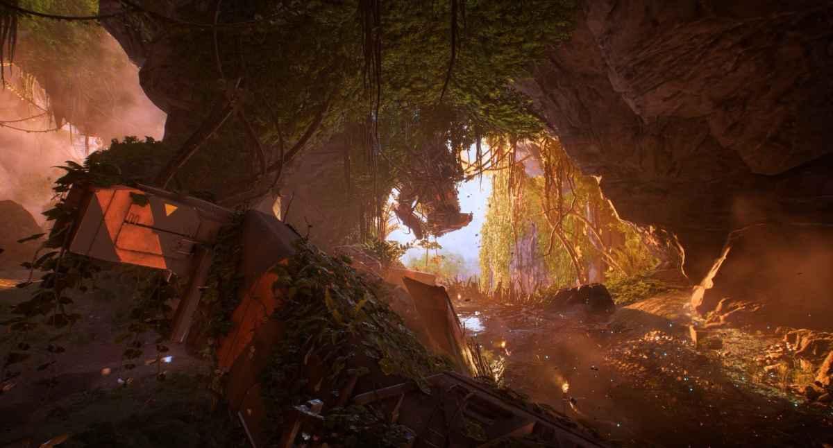 Screenshot di Anthem che raffigura una grotta lussureggiante con dentro il relitto di un veicolo