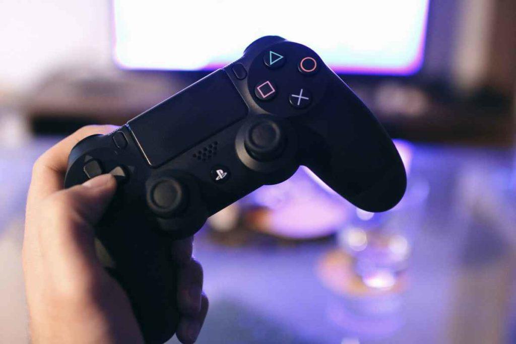 Foto di una persona che tiene in mano un dualshock della Playstation 4