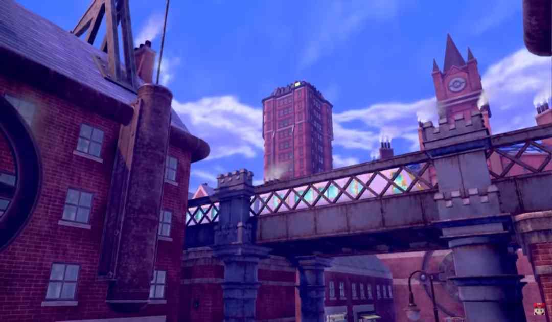 Screenshot dal trailer che mostra un treno sfrecciare all'interno della metropoli dai mattoni rossi