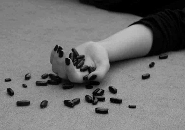 L'immagine, in bianco e nero, mostra la mano di una ragazza evidentemente svenuta contenente alcune pillole scure