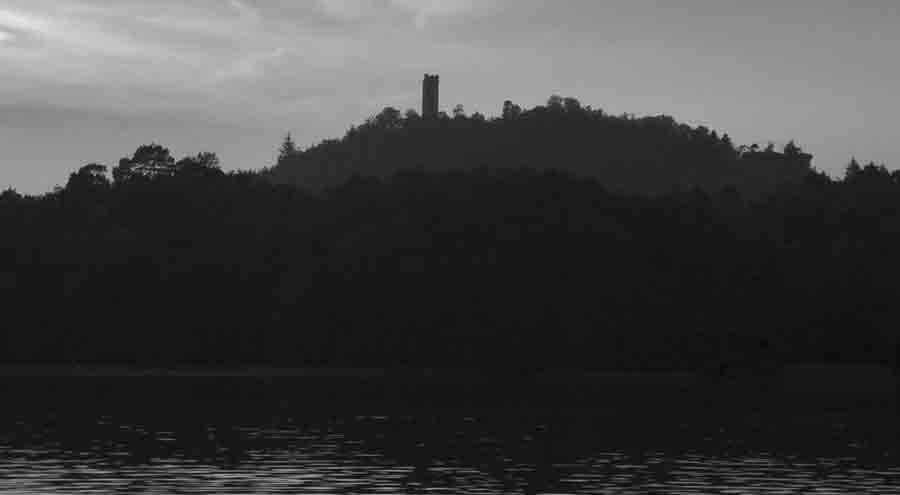 L'immagine, in bianco e nero, mostra lo scenario di questa storia inquietante: dalle acque di un lago emergono alcuni rilievi coperti da vegetazione. In cima svetta la sagoma di una torre solitaria.