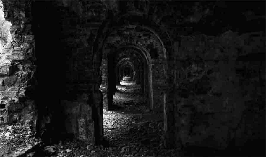 Immagine in toni di grigio: l'interno di un edificio in rovina, nel quale una serie di porte sembra creare un corridoio