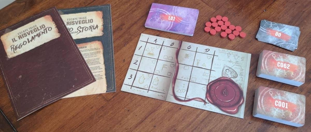 i libri del regolamento e della storia, affiancati dalla plancia a griglia per i luoghi, i token rossi e le carte da gioco