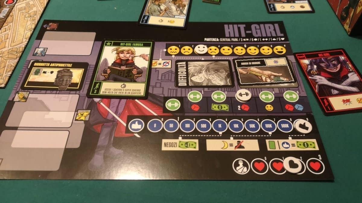 la plancia di gioco di hit girl durante la partita con le carte difficoltà girate e la carta azione hit girl famosa a disposizione