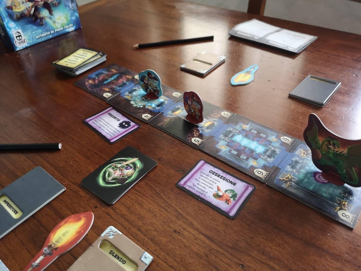 il setup di trapwords, con le torce, il libri per le squadre, le carte trappola e gli stand posizionati sul dungeon