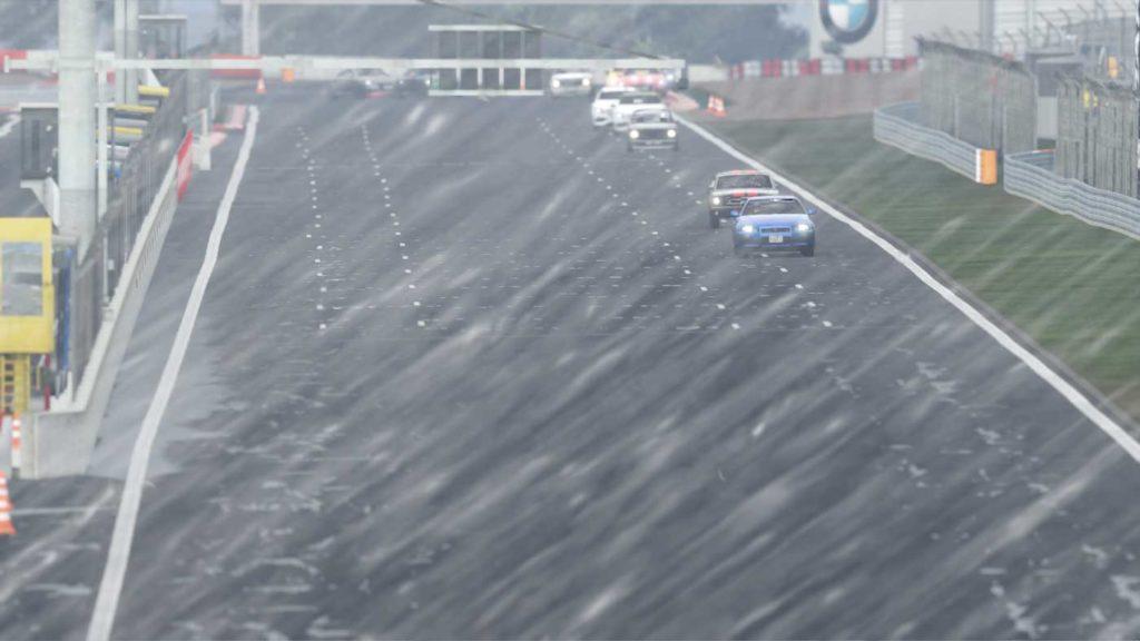 Foto di gara con la pioggia. Un serpente di auto con le pozzanghere intorno